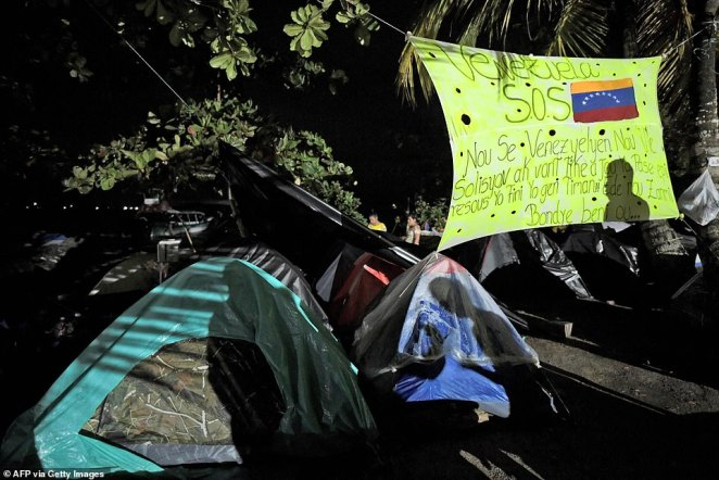 Haitian migrants offer support to Venezuelans in Necocli as they all remain stranded waiting for boats to cross into neighboring Panama on their way to the United States
