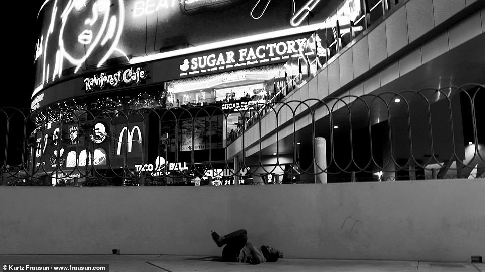 Hidden: One of Frausun's photos from the series shows someone lying on the ground below bright lights of the restaurants packed with patrons
