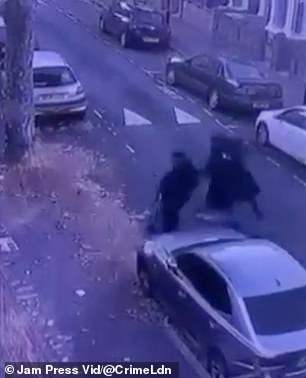 The two suspected thieves are seen approaching the victim from behind and dragging him to the ground