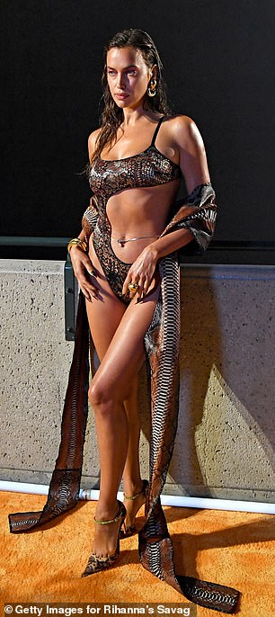 Wild side: Irina caught the eye in a sexy snakeskin bodysuit with a large cutout on the front that exposed her taut stomach