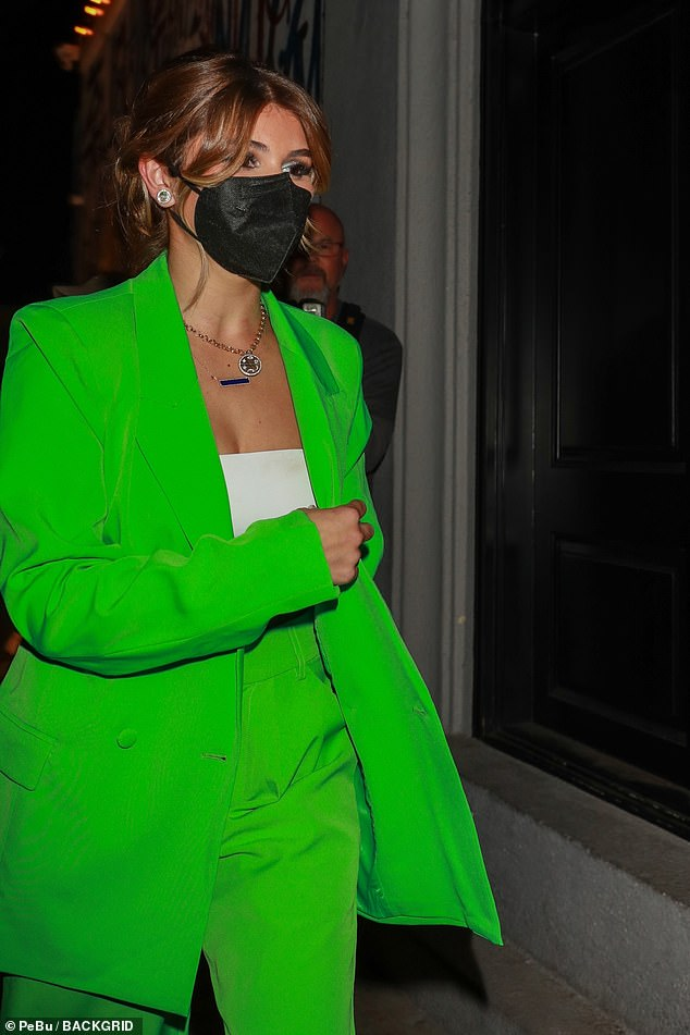 On-the-go: The 22-year-old influencerdonned an oversized green suit over a white bandeau top and completed the look with a pair of white and green sneakers