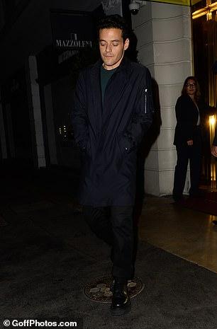 Hunk: Meanwhile, Rami cut a dapper figure in a longline black coat and matching tailored trousers