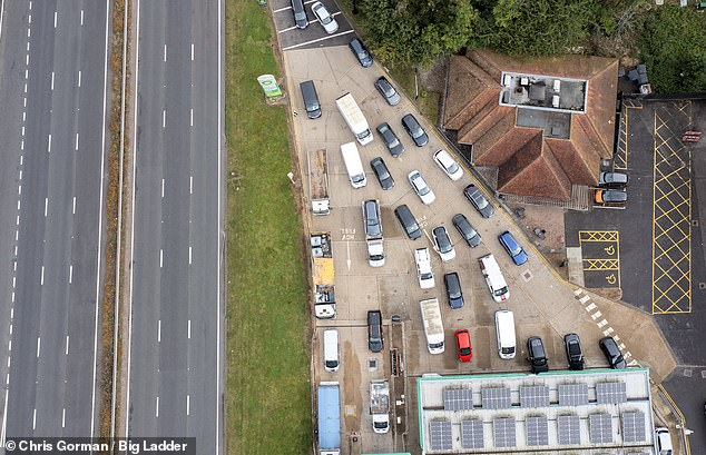Drivers line up for fuel at petrol stations (Picture: Wisley South Services in Surrey today. The local council is considering declaring a state of emergency)