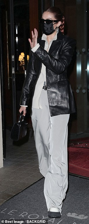 Cozy:The 26-year-old runway maven rocked a light grey zip-up top and a pair of matching ultra flared trousers
