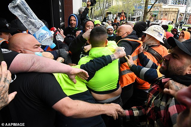 Violent scenes in Melbourne erupted on Monday when construction workers angry about vaccination mandates mobbed the headquarters (pictured)