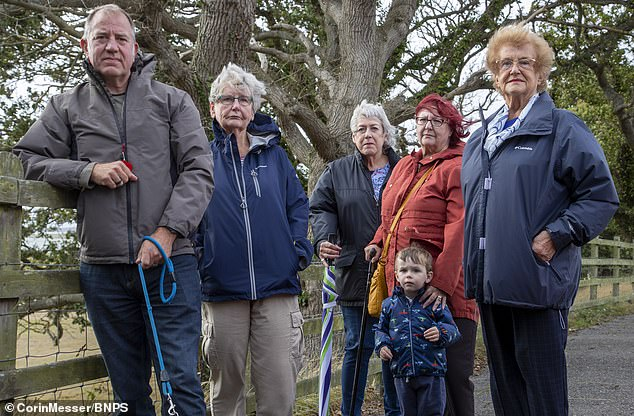 John Challinor, the chairman of the Parkstone Bay Residents Association, pictured with residents next to the two dead oak trees. Mr Challinor said: 'If everyone had the view they wanted, we wouldn't have any trees'