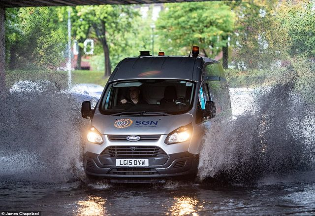 Britain is bracing itself for snow and floods with temperatures plummeting by 10C as wintry conditions start to take hold. Pictured: a car drives through floods in Glasgow today