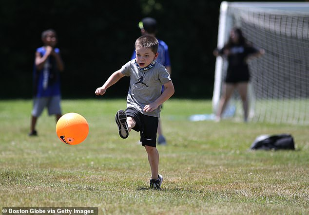 Nine people tested positive, including three immunization staff members and six unvaccinated children between the ages of eight and 14, with none of the cases linked to camp transmission.  Image: A camper attends a football game at the Denver YMCA Summer Camp in Denver, Massachusetts in July 2020