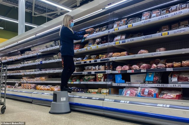 A staff member on an isle at a Tesco store in Swansea, south Wales (stock image)