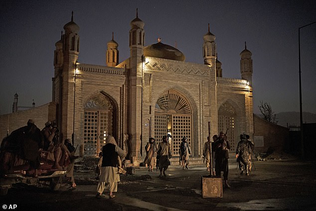 Taliban fighters walk at the entrance of the Eidgah Mosque after the bombing, which cause little damage to the mosque but killed several civilians. Damage to the mosque gates and archway can be seen above