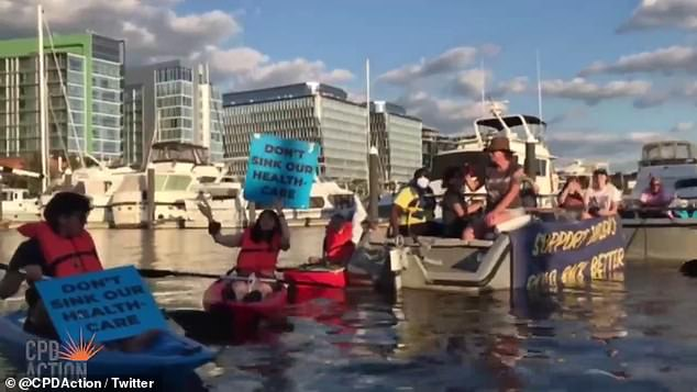 Protesters kayaked to the ship to ask why their senator would not support his own party's $3.5 trillion infrustructe bill