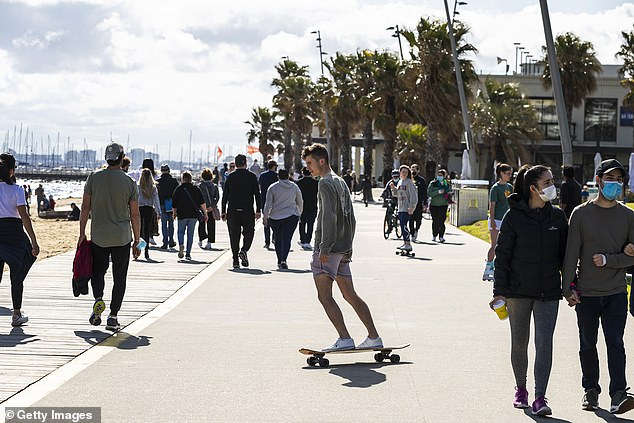 There are currently 498 people hospitalised with Covid-19 with 96 in ICU and 59 on ventilators (pictured, people gather in St Kilda in Melbourne)