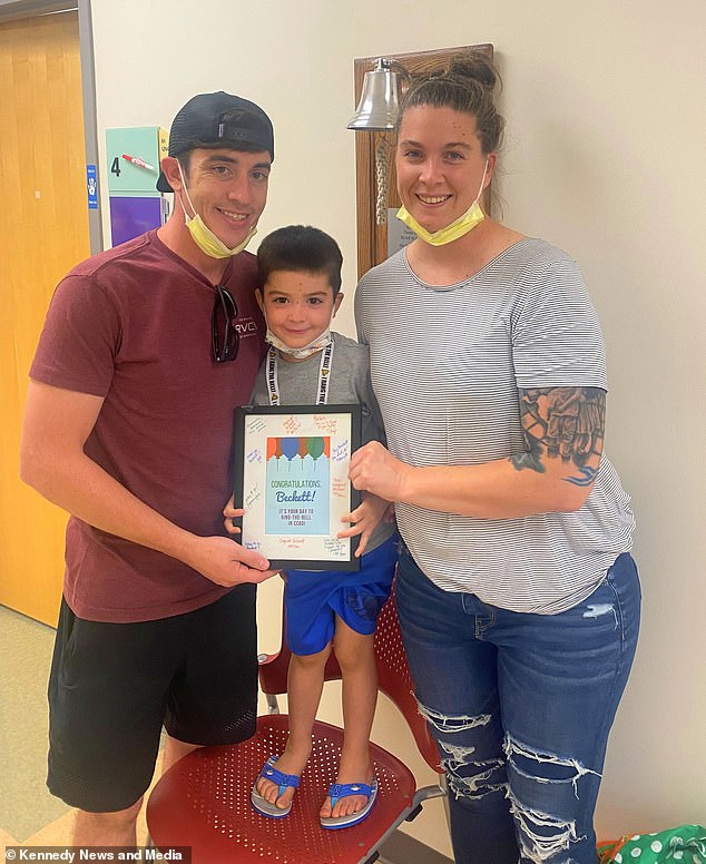 Caitlin and her husband Matthew help congratulate their little boy after he finishes his treatment