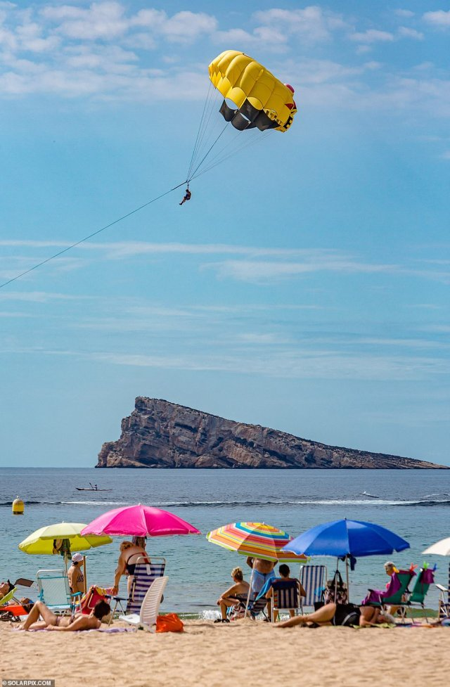 A daredevil takes to the skies above a group of sunbathers as Britons pack out the beaches and work on their tans in Benidorm