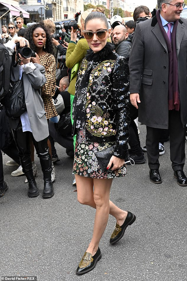 Stepping out: The socialite showed off her skinny pins in a floral mini-dress with a high ruffled neckline and a black leather clutch in her hand.