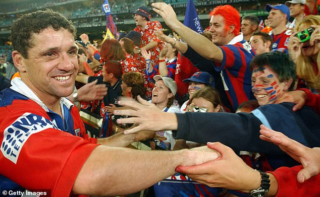 The decision to fine the Knight's star has been met with outrage in the rugby league-mad community (pictured) Robbie O'Davis pictured being swamped by fans after the 2001 Grand Final