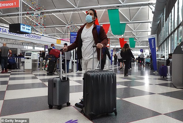 The CDC removed holiday travel guidelines posted over the weekend from its website, saying they were out of date and published in error.  The guidelines recommended virtual gatherings.  Pictured: A man wears a mask while traveling at O'Hare International Airport in Chicago, Illinois, the last holiday season on December 23
