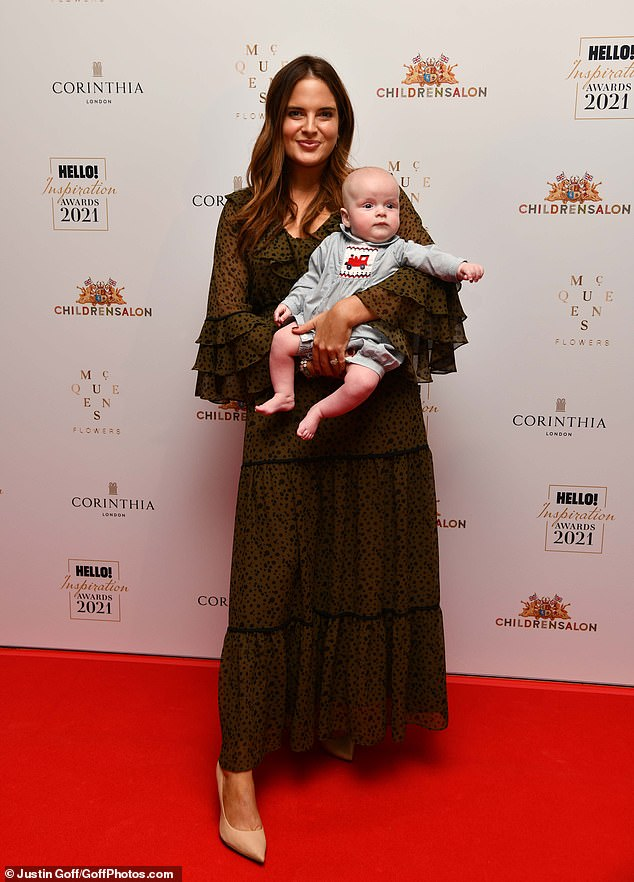 Stunning: Binky cradled her youngest child in her arms while wearing a gorgeous khaki ruffled maxi dress, while Wulfric wore a cute grey romper with a red tractor on the front