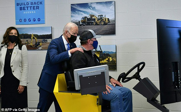 President Joe Biden is shown how simulators for heavy equipment work at theInternational Union of Operating Engineers Training Facility in Howell, Michigan on Tuesday, alongside Michigan Gov. Gretchen Whitmer