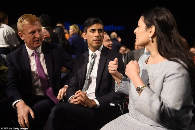 (L-R) Britain's Conservative Party charperson Oliver Dowden, Chancellor of the Exchequer Rishi Sunak and home Secretary Priti Patel chat as they wait for the keynote speech