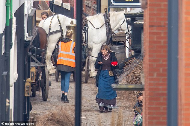 The actress, 17, wore a traditional period costume layered beneath a warm navy coat while glued to her phone in-between takes of the Netflix sequel