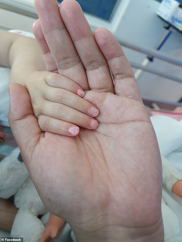 A moving photo shows little Charlotte's tiny hand in his in the hospital bed, her nails still painted a soft shade of pink