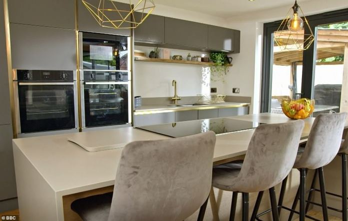 Heart of the home: The couple were given much-needed counter space, plus in-built appliances, as part of a high-end renovation (pictured).  Couple Added a Kitchen Island and Gold Touches for an Ultra-Luxe Feel