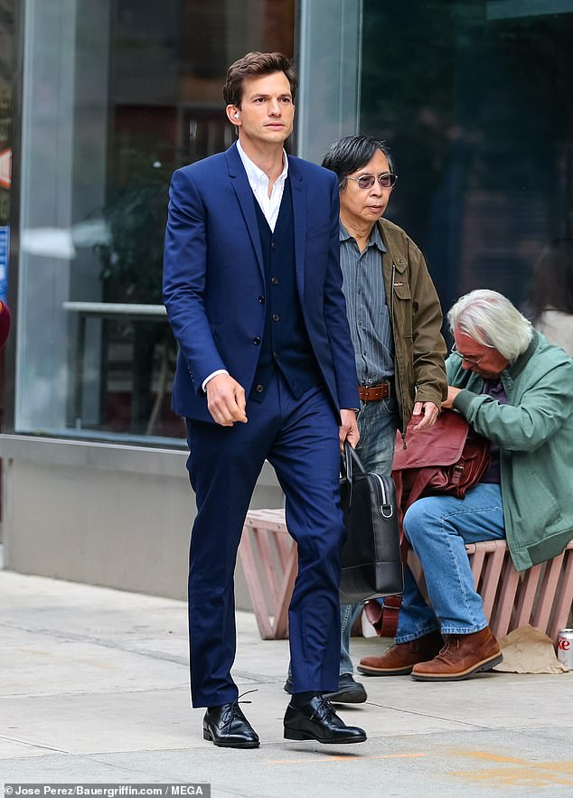 Hollywood hunk:Ashton Kutcher was also spotted filming a scene looking debonair dressed in a smart, tailored blue suit, blue vest and white button-down