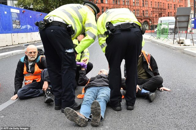 Several protesters glued themselves onto the road - a familiar tactic - forcing officers to use a chemical solution to release them