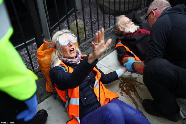 These two activists appeared to have glued themselves together. An officer is seen trying to release them