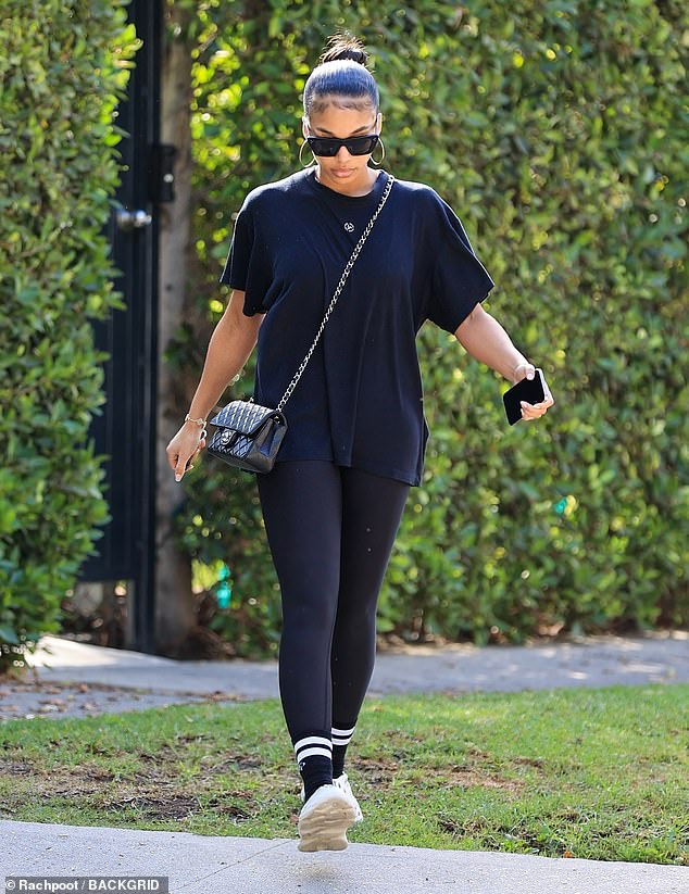 Athleisure look: The fashionista extended the comfortable look with black socks that had two white stripes, and a pair of Yeezy Foam RNNR sneakers