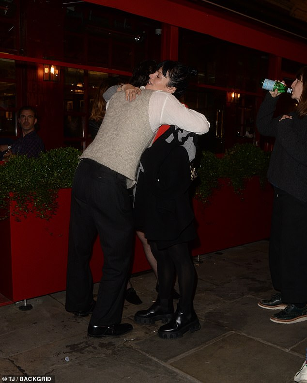 Farewell: Tying up her silky raven locks, the Smile hitmaker hugs a group of her friends before heading home