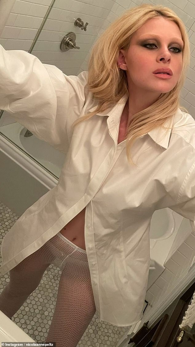 Sexy: Nicola Peltz once again showed her cheeky side on Instagram Friday night in fishnet tights and a buttonless white shirt