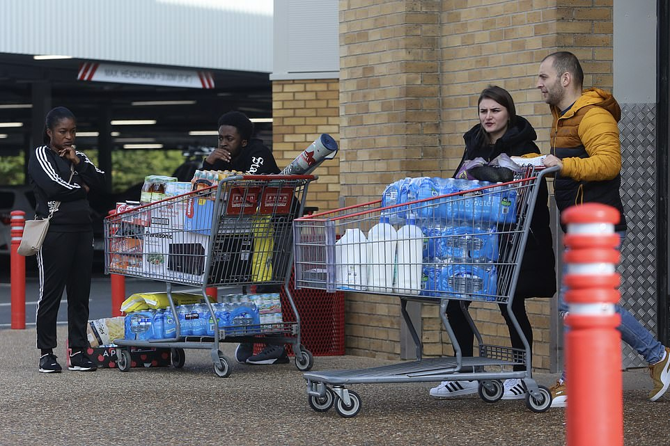Shoppers seen pushing trolleys laden with water bottles as they stock up at a Costco superstore in Bushey, Hertfordshire