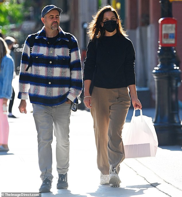 Casual:The Batman Begins actress donned a high-necked black sweater along with a pair of wide-leg pleated tan trousers for her outing on the sunny afternoon
