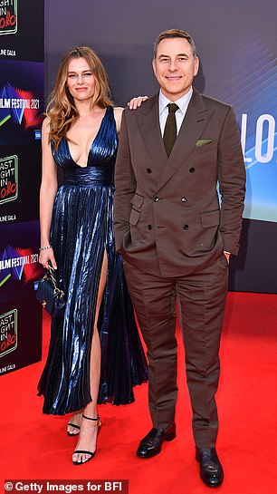David's companion sent temperatures soaring as she flashed her ample assets in a glossy blue maxi dress featuring a tantalising thigh-slit