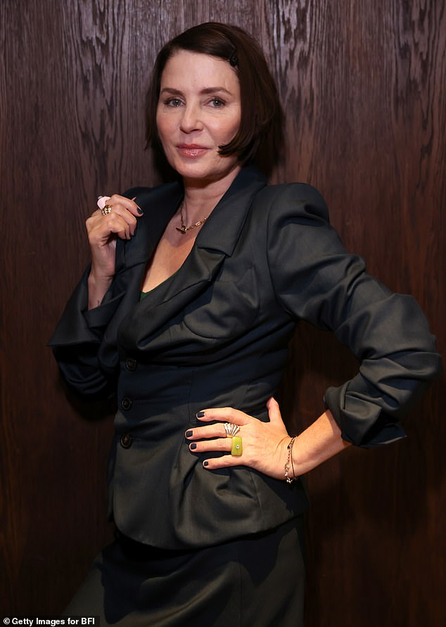 Stylish: The fashion designer posed for a portrait at the event which saw her wearing a navy blue skirt suit