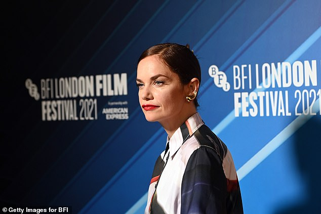 Stunning: She swept her brunette locks into a sleek bun and her glam makeup was completed with a slick of red lipstick