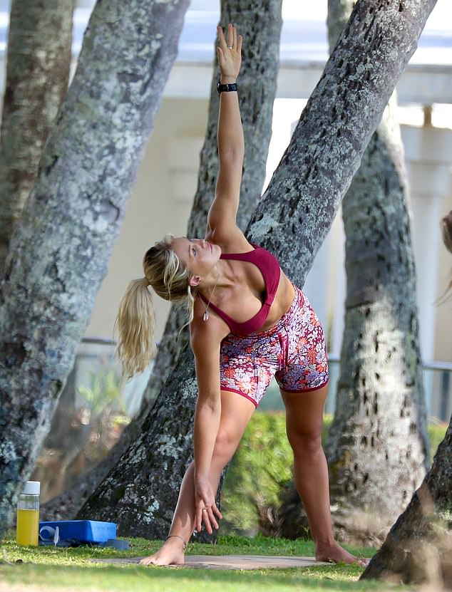 Stretching it out:Ali looked fit as a fiddle, revealing her taut abdominals in a red sports crop top and high-waisted floral bike shorts