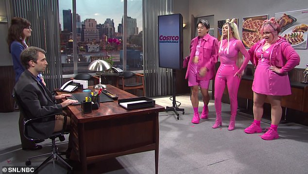 Pretty in pink: The three singers of Glitter Revolution march into the office, with Kim standing in the center in a sheer pink top with a vinyl bust and matching pants, as well as tall boots