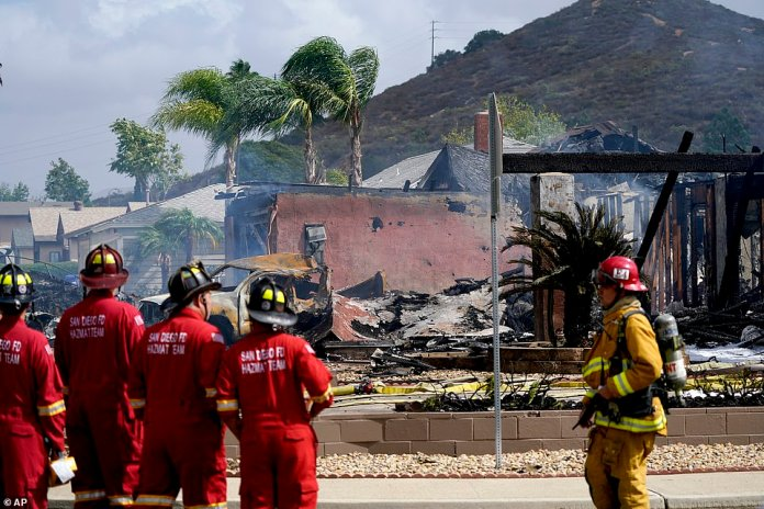 Fire crews work the scene of a small plane crash in Santee. At least two people were killed and two others were injured when the plane crashed into a suburban Southern California neighborhood, setting two homes ablaze