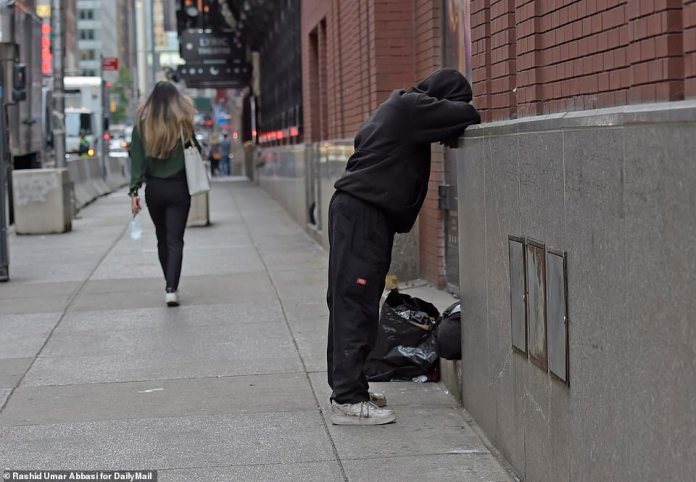 Homeless person is seen supporting himself against a wall on 43rd street around Times Square in Manhattan