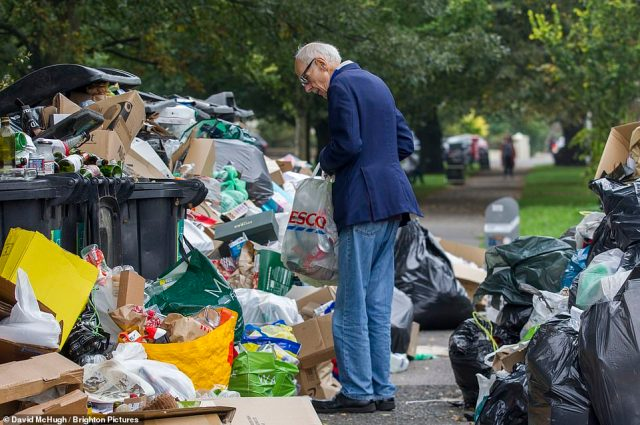 People struggle to find a pathway through the mountains of rubbish piled up in Montpelier Crescent in Brighton