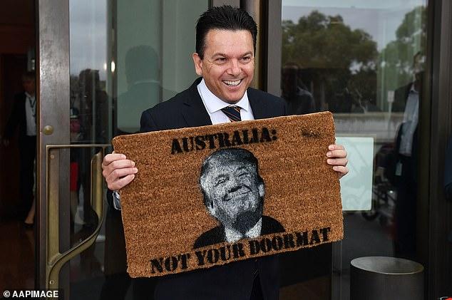 Senator Nick Xenophon arrives at the Senate entrance holding a novelty doormat in 2017