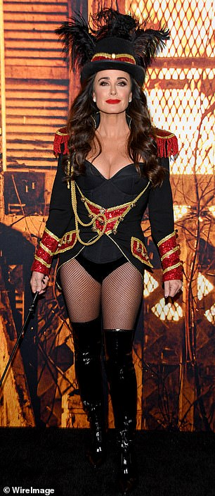 Details: The 52-year-old reality star's getup consisted of a black high-legged leotard and a black, gold, and red jacket with fringed shoulder pads