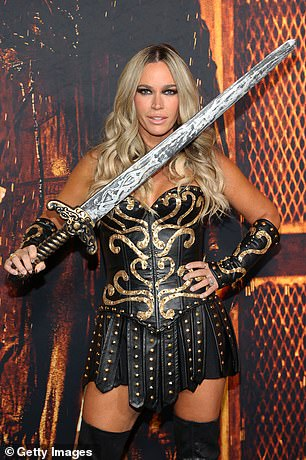 Ready for battle: The 40-year-old fitness guru wielded a sword and wore her bright blonde strands in voluminous curls