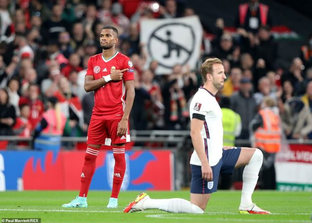 Trouble started after England's players took the knee before kick-off in a gesture against racism - and in the Hungarian section of the crowd there was a banner protesting against the act of taking the knee, seen here behind England captain Harry Kane