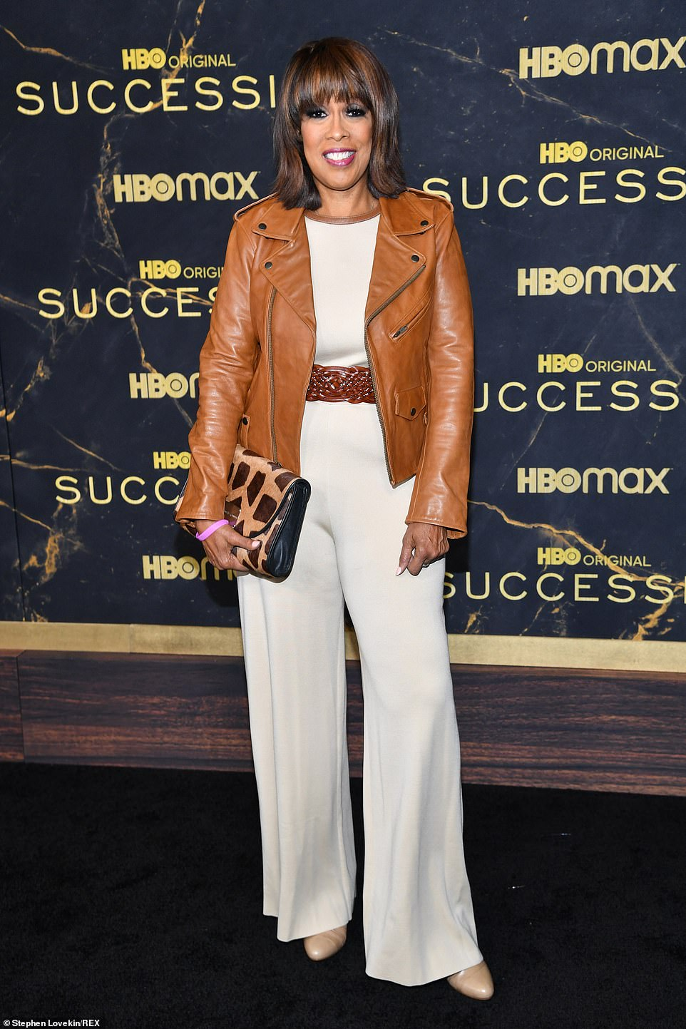 Say cheese!Gayle King flashed a huge smile as she cut a stylish figure in white jumpsuit and a brown leather jacket