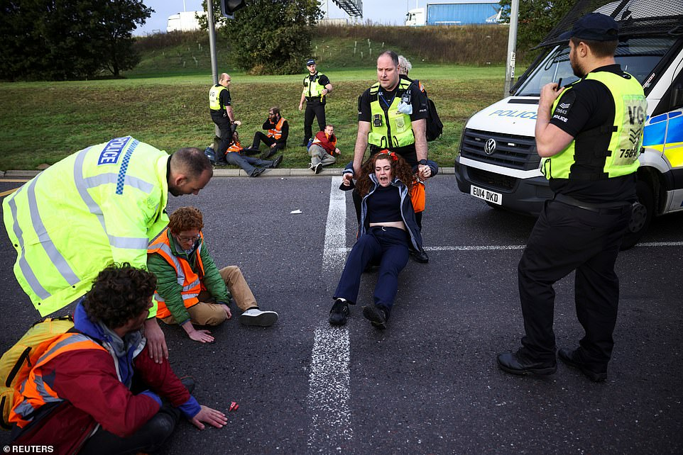Police officers detain Insulate Britain activists blocking a roundabout on the M25 this morning