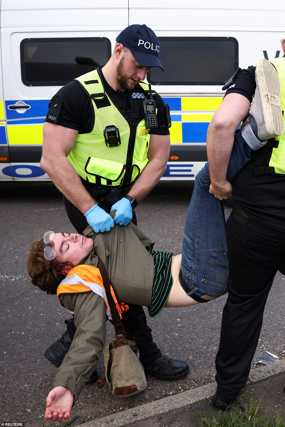 Police officers detain a man as Insulate Britain activists block a roundabout at junction 31 of the M25 in Thurrock today